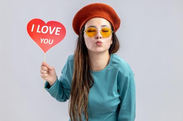 Z zamkniętymi oczami młoda dziewczyna na walentynki w kapeluszu w okularach trzymając czerwone serce na patyku z tekstem kocham cię pokazując gest pocałunek na białym tle