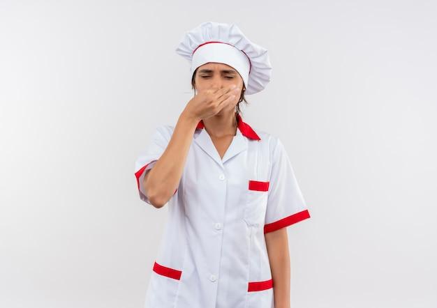 Z zamkniętymi oczami młoda kobieta kucharz ubrana w mundur szefa kuchni zamknięty nos z miejsca na kopię