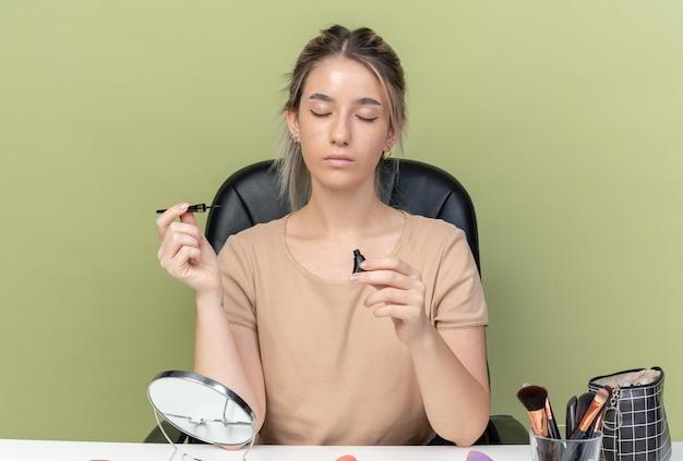 Z zamkniętymi oczami młoda piękna dziewczyna siedzi przy stole z narzędziami do makijażu, trzymając tusz do rzęs na oliwkowym zielonym tle