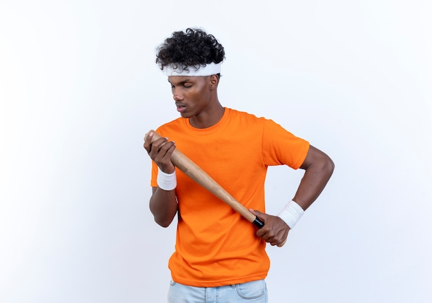 Z zamkniętymi oczami młody afroamerykański sportowy mężczyzna w opasce na głowę i nadgarstku trzyma nietoperza