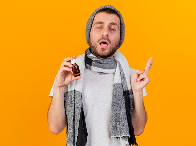 Z zamkniętymi oczami młody chory w czapkę zimową i szalik trzymając lekarstwa w szklanej butelce na białym tle na żółtym tle