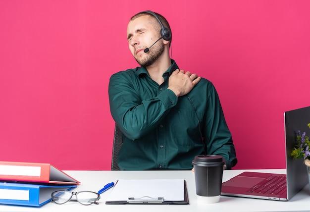 Z zamkniętymi oczami młody mężczyzna operator call center noszący zestaw słuchawkowy siedzący przy biurku z narzędziami biurowymi chwycił bolące ramię
