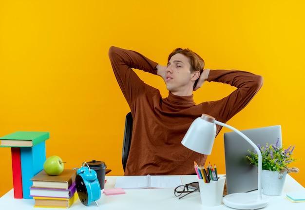 Z zamkniętymi oczami młody uczeń chłopiec siedzi przy biurku z narzędzi szkolnych, trzymając ręce za głową