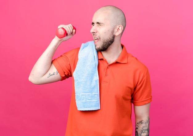 Z zamkniętymi oczami napięty młody sportowy mężczyzna ćwiczy z hantlami z ręcznikiem na ramieniu na białym tle na różowej ścianie
