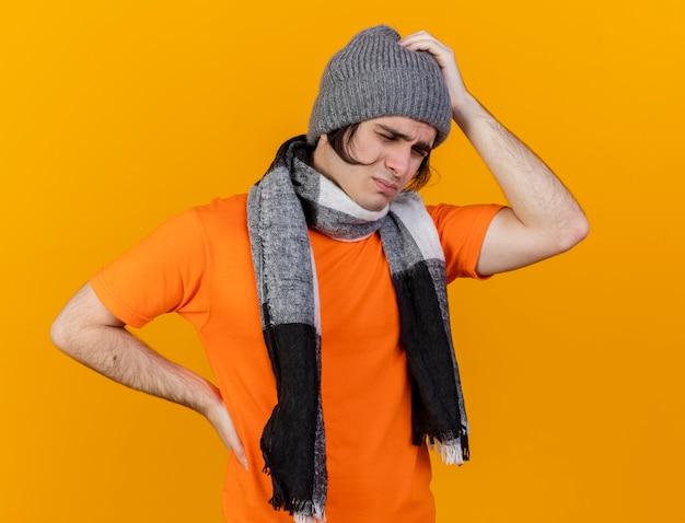 Z zamkniętymi oczami niezadowolony młody chory w czapce zimowej z szalikiem kładzie ręce na bolącej głowie i biodrze na białym tle na pomarańczowym tle