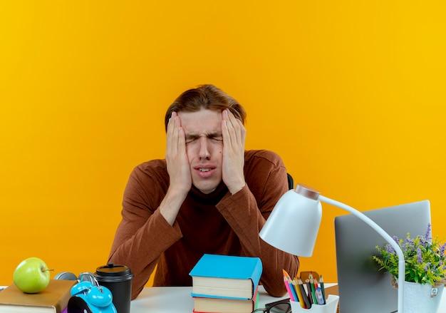 Z zamkniętymi oczami podkreślił młody uczeń chłopiec siedzi przy biurku z narzędziami szkolnymi kładąc ręce na policzkach na żółto