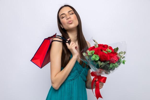 Z zamkniętymi oczami pokazującymi gest pocałunku piękna młoda dziewczyna na szczęśliwy dzień kobiety trzymająca bukiet, kładąc torbę na prezent na ramieniu na białym tle na białej ścianie
