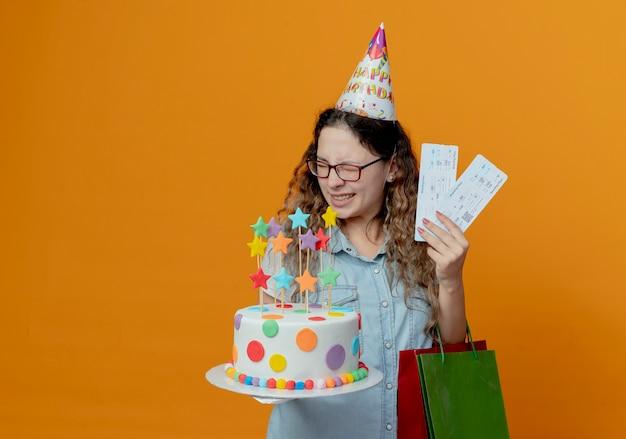 Z zamkniętymi oczami radosna młoda dziewczyna w okularach i czapce urodzinowej, trzymając bilety i tort urodzinowy z torbami na prezenty na białym tle na pomarańczowym tle