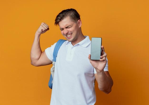 Z zamkniętymi oczami radosny młody przystojny student płci męskiej na sobie tylną torbę trzymając telefon