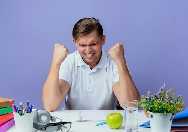 Z zamkniętymi oczami radosny młody przystojny student płci męskiej siedzi przy biurku z narzędziami szkolnymi pokazując gest okey na niebieskim tle