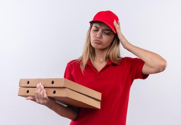 Z zamkniętymi oczami smutna młoda dziewczyna dostawy ubrana w czerwony mundur i czapkę, trzymając pudełka po pizzy i kładąc rękę na głowie na białym tle