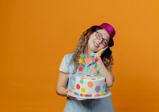 Z zamkniętymi oczami uśmiechnięta przechylająca głowę młoda dziewczyna w okularach i różowym kapeluszu