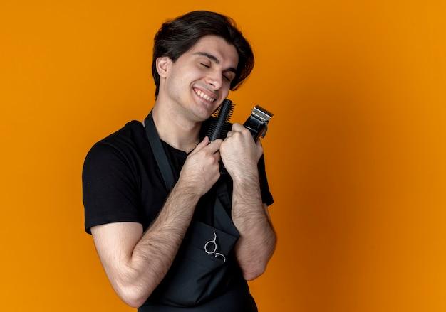 Z zamkniętymi oczami zadowolony młody przystojny mężczyzna fryzjer w mundurze, trzymając maszynkę do strzyżenia włosów i nożyczki wokół serca odizolowane na pomarańczowo