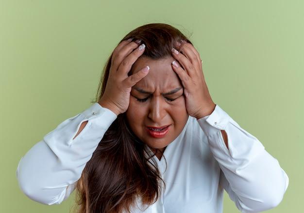 Z zamkniętymi oczami zaniepokojona przypadkowa kaukaska kobieta w średnim wieku złapała się za głowę