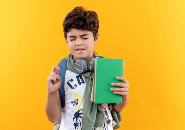 Z zamkniętymi oczami zaniepokojony mały szkolny chłopiec w torbie i słuchawkach, trzymający książkę i krzyżujący palce