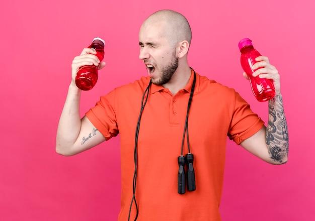 Z zamkniętymi oczami zły młody sportowy mężczyzna trzymający butelki z wodą ze skakanką na ramieniu odizolowanym na różowej ścianie
