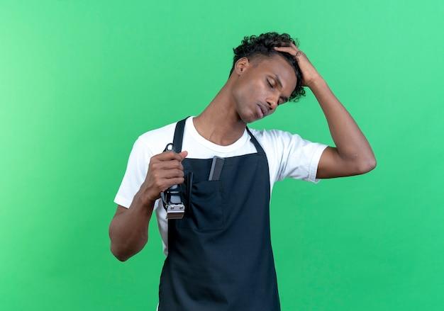Z zamkniętymi oczami zmęczony młody afro-amerykański mężczyzna fryzjer w mundurze, kładąc dłoń na głowie i trzymając maszynkę do strzyżenia włosów na białym tle na zielonej ścianie
