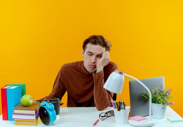 Z zamkniętymi oczami zmęczony młody uczeń chłopiec siedzi przy biurku z narzędziami szkolnymi, kładąc głowę na nadgarstku na białym tle na żółtej ścianie