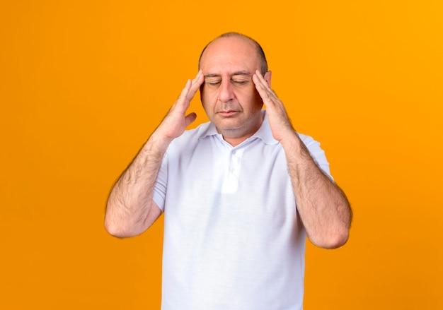 Z zamkniętymi oczami zmęczony przypadkowy dojrzały mężczyzna kładący ręce na świątyni odizolowanej na żółtej ścianie