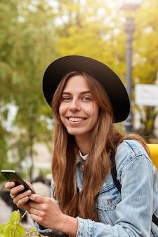 Z zewnątrz ujęcie szczęśliwej europejki z przyjemnym uśmiechem, trzyma nowoczesną komórkę, sprawdza skrzynkę mailową, cieszy się słonecznym dniem, sms-y