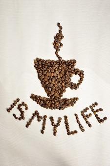 Z ziaren kawy ułożona jest figura w kształcie filiżanki kawy ze spodkiem