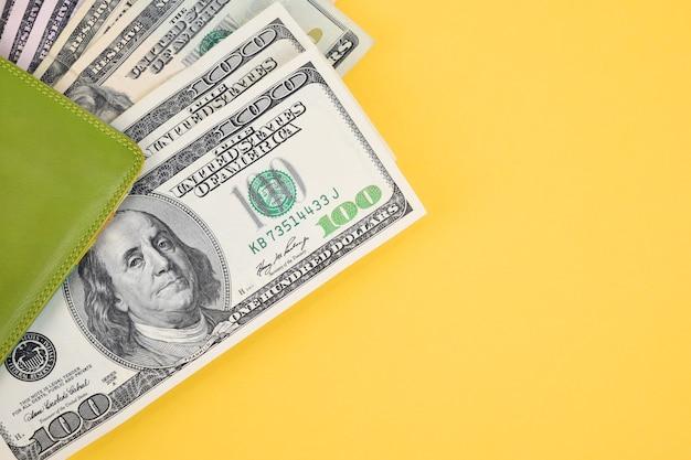 Z zielonego skórzanego portfela wystają banknoty stu dolarowe