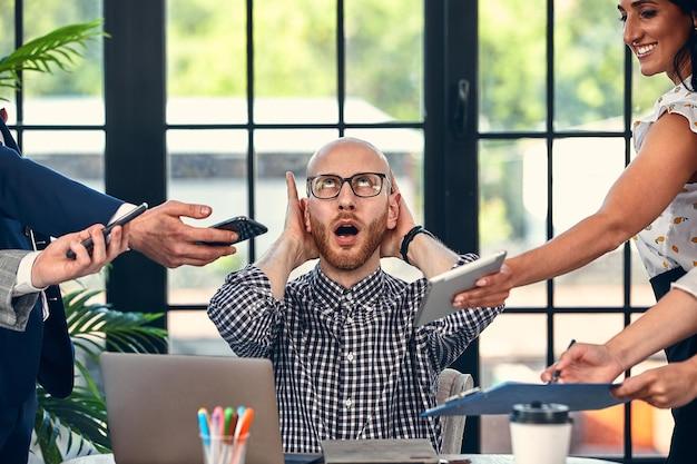 Za dużo pracy. selektywne skupienie młodego biznesmena w otoczeniu kolegów, każdy proponuje projekt, prosi o akceptację lub podpisanie. ostateczny termin.