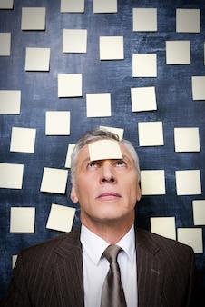 Za dużo pracy. sfrustrowany starszy mężczyzna w stroju formalnym z samoprzylepną notatką na czole, patrzący w górę, stojący przed tablicą