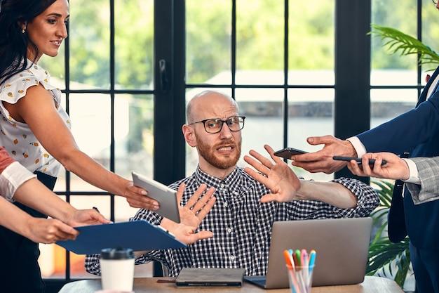 Za dużo pracy. wybiórcze skupienie młodego biznesmena w otoczeniu kolegów, każdy proponuje projekt, prosi o zatwierdzenie lub podpisanie. ostateczny termin.