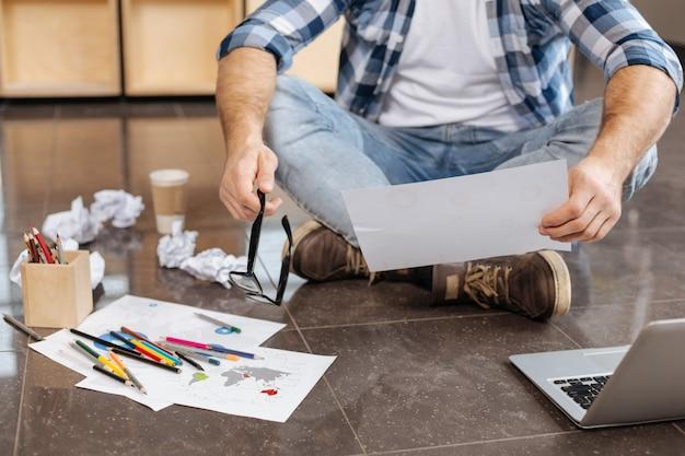 Za dużo pracy. zmęczony miły ciężko pracujący mężczyzna siedzi na podłodze i zdejmuje okulary podczas pracy