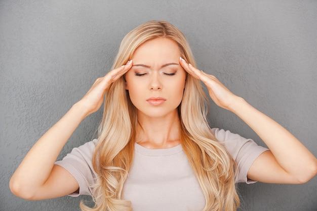 Za dużo stresu. przygnębiona młoda kobieta o blond włosach dotykająca czoła i trzymająca zamknięte oczy