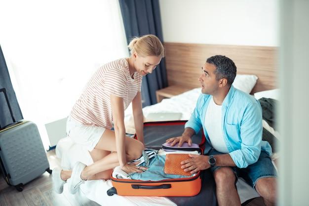 Za dużo ubrań. ostrożny mąż i żona wpychają ubrania do walizki podróżnej, starając się ją zmniejszyć.