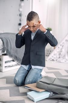 Za dużo zadań. zmartwiony afroamerykański chłopiec masuje skronie, siedząc na podłodze w domu