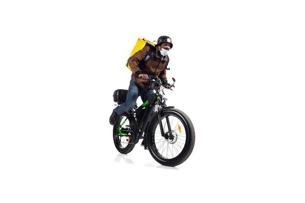 Za dużo zamówień. bezdotykowa usługa dostawy podczas kwarantanny. mężczyzna dostarcza jedzenie podczas izolacji, nosząc kask i maskę na twarz. biorąc jedzenie na rowerze na białym tle na białej ścianie. bezpieczeństwo. spiesząc się.
