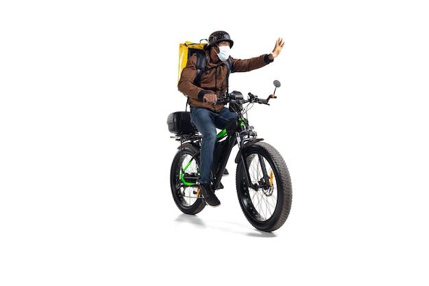 Za dużo zamówień. bezkontaktowa usługa dostawy podczas kwarantanny. mężczyzna dostarcza jedzenie podczas izolacji, nosząc kask i maskę na twarz. biorąc jedzenie na rowerze na białym tle na białej ścianie. bezpieczeństwo. spiesząc się.