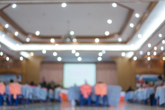Za groub publiczność przemawia do mówcy w sali konferencyjnej lub sali seminaryjnej z rozmytymi jasnymi ludźmi
