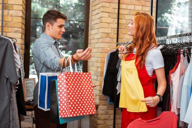Za jasno. młody człowiek robi zakupy ze swoją wesołą, podekscytowaną dziewczyną i czuje się zaskoczony, widząc ją trzymającą jasne ubrania