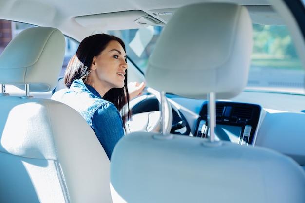 Za kierownicą. atrakcyjna, miła młoda kobieta siedzi w samochodzie i prowadzi go będąc zręcznym kierowcą