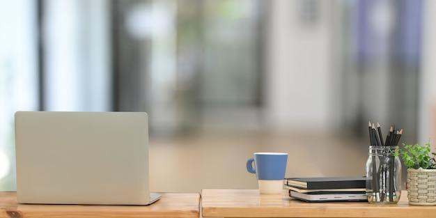 Za komputerem laptop kładzie się na drewnianym biurku otoczonym akcesoriami biurowymi.