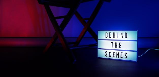 Za kulisami lightbox. tekst na podświetlanym kinie. obok megafon i krzesło reżysera oraz tablica filmowa. koncepcja za kulisami.