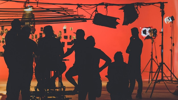 Za kulisami z kamerzystą kręcącym film wideo z ekipą produkcyjną ustawiającą scenę