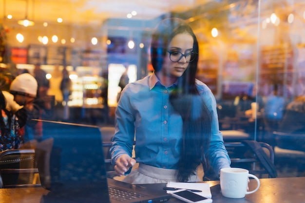 Za oknem kobieta siedzi w okularach i pije kawę