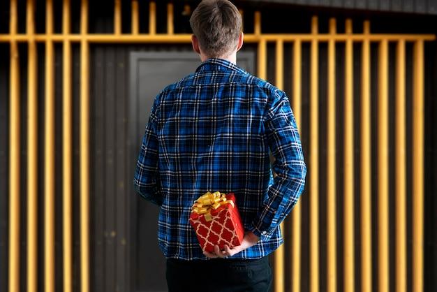 Za plecami trzyma pudełko upominkowe dla mężczyzny prezent niespodzianka