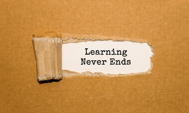 Za podartym brązowym papierem pojawia się tekst nauka nigdy się nie kończy