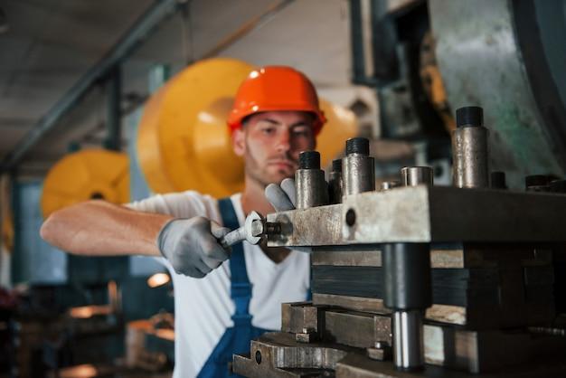 Za pomocą klucza. mężczyzna w mundurze pracuje nad produkcją. nowoczesna technologia przemysłowa.