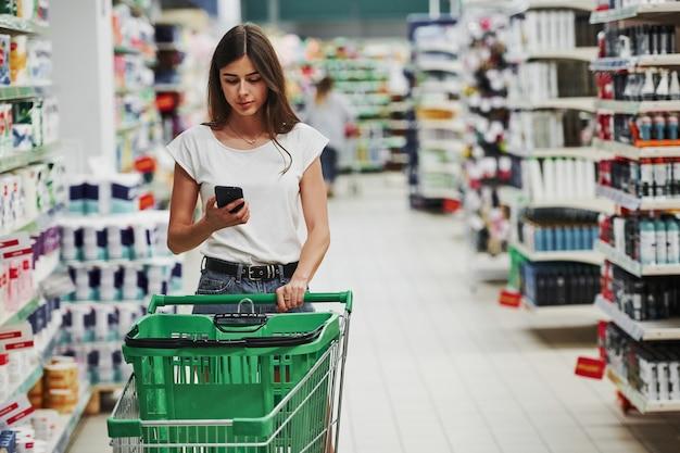 Za pomocą smartfona. kobieta shopper w ubranie na rynku poszukuje produktów.
