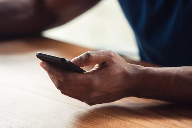 Za pomocą smartfona. zamknij się z afro-męskich rąk, pracując w biurze. pojęcie biznesu, finansów, pracy, zakupów online lub sprzedaży. miejsce na reklamę. edukacja i freelancer.