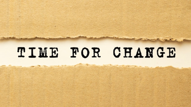 Za rozdartym brązowym papierem pojawia się napis czas na zmiany. widok z góry.