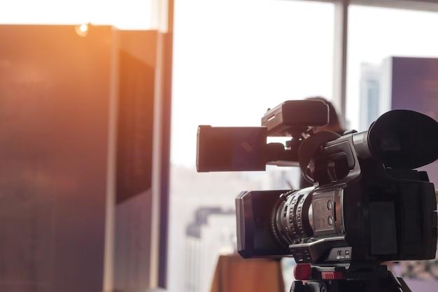Za sceną nagrywania kamery wideo strzelanie do sali konferencyjnej na żywo mikrofon wifi wysyłający do prezentacji z jasnym tłem. koncepcja wywiadu przy produkcji mediów