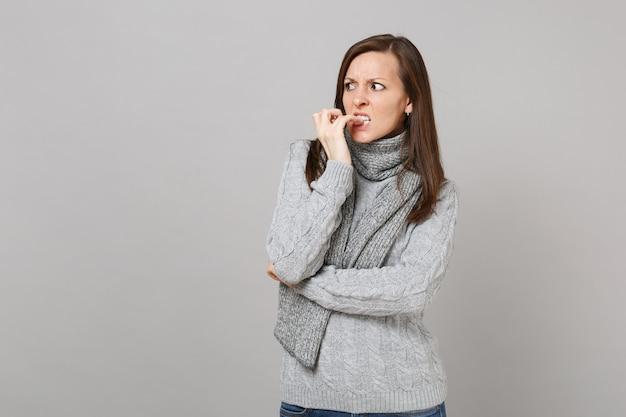 Zaabsorbowana młoda kobieta w szarym swetrze, szalik patrząc na bok, obgryzając paznokcie na białym tle na szarym tle ściany. zdrowa moda styl życia ludzie szczere emocje koncepcja zimnej pory roku. makieta miejsca na kopię.
